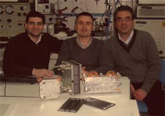 Dr. Giosuè Giacoppo et Dr. Gaetano Squadrito (CNR-ITAE) entourent Bruno Auvity (enseignant-chercheur à Polytech Nantes). Au premier plan, quelques prototypes et éléments de piles à combustible développés au CNR-ITAE.