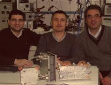 Dr. Giosuè Giacoppo et Dr. Gaetano Squadrito (CNR-ITAE) entourent Bruno Auvity. Au premier plan, quelques prototypes et éléments de piles à combustible développés au CNR-ITAE.